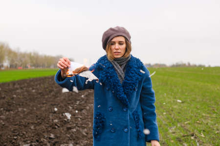 Beautiful girl stay outdoors in blue coat in open field, burn white paper and ash fly around with wind