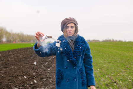 Beautiful girl in blue coat and beret stay alone at windy field and burn white paper, ash fly around, making ritual
