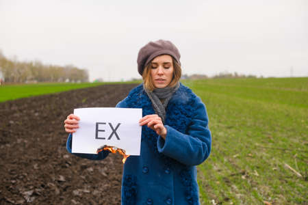 Beautiful sad girl stay at field with closed eyes and hold paper with text Ex about broken up relations, divorce, finished love