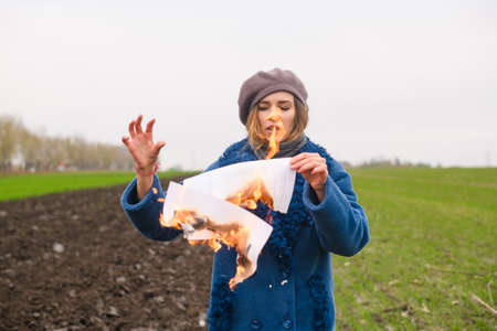 Desperate angry girl in blue coat hold burning paper with fire at open cold windy field, female frustration and sadness, start life from new page