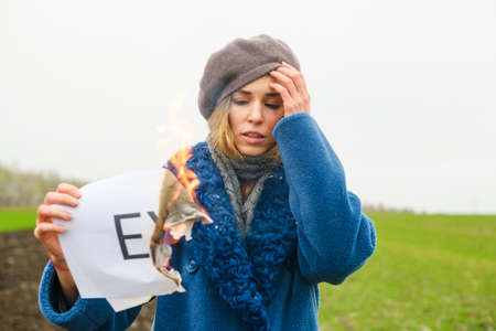 Sad girl hold burning paper with fire and printed word Ex about boyfriend, husband, broken up relations, divorce ritual