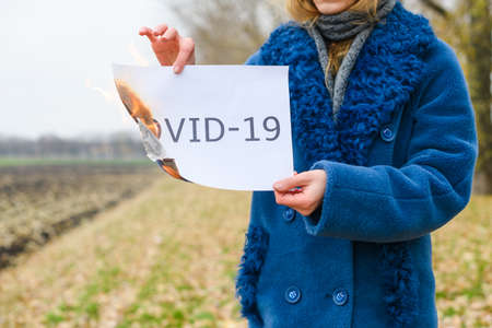 Woman in blue coat stay at open isolated area and burn paper sheet with printed text Covid-19, stop epidemy