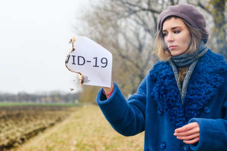 Frustrated girl with tears stay at open field and hold paper sheet with printed text Covid-19, against pandemic world