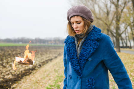Beautiful decisive girl in blue coat stay at open field with flying burning paper in fire, ritual to start better life 스톡 콘텐츠