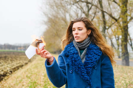 Frustrated young beautiful woman in blue coat stay at open area with smeared makeup and hold burning paper with flame