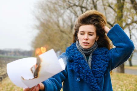 Frustrated young beautiful woman stay at field and hold burning white paper sheet with fire and flame, fighting depression 스톡 콘텐츠