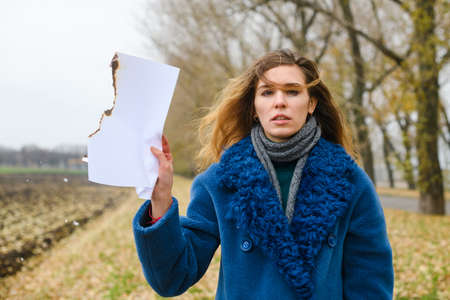 Frustrated young woman with smeared makeup mascara after crying, in blue coat, stay at field and hold burning smolder blank white paper