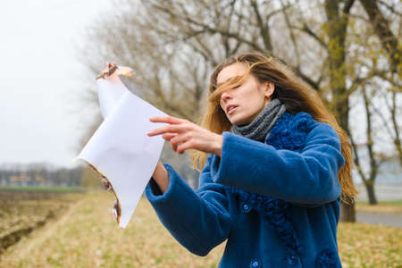 Beautiful young woman in blue coat stay at open windy area and hold flying burning paper sheet with flame and smolder