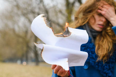 Sad woman in depression cover her face with hand and hold white blank burning paper in fire and smolder outdoors 스톡 콘텐츠