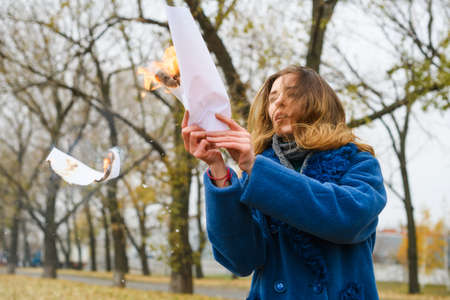 Beautiful girl in blue coat make ritual with burning white paper sheet at nature background, fighting depression