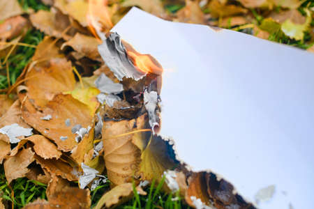 Close up set on fire burning white paper sheet and fall dry yellow foliage with flame, smolder and ash