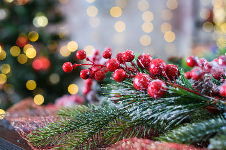 Close up Christmas and New year tree with decoration of viburnum red berries, covered with snow, light bokeh at background