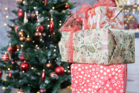 Three decorated present boxes in craft paper with bows for New year and Christmas holiday and fir tree with toys ball on branches at background 스톡 콘텐츠