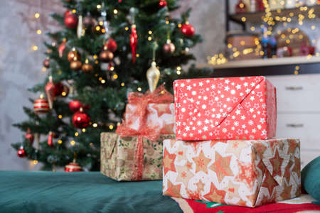 Decorated room with fir tree with red and golden ball ornaments, light garlands, gift boxes for Christmas and New year holidays