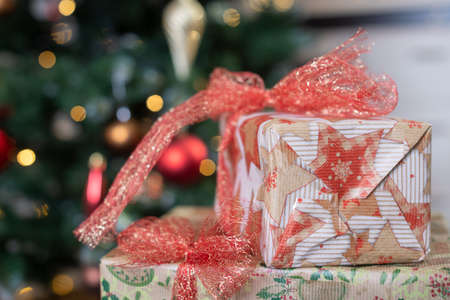 Close up gift present boxes for New year and Christmas holidays covered by craft paper with red bows at beautiful fir tree background