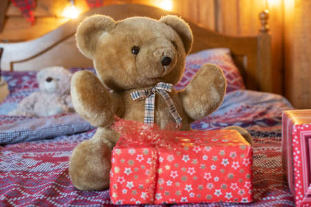 Cute brown teddy bear toy sit on bed near red Christmas and New year eve gift box with bow, presents for kids