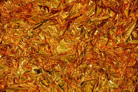 Gold foil background with shiny crumpled surface for texture background 스톡 콘텐츠