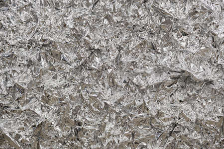 Silver foil background with shiny crumpled surface for texture background