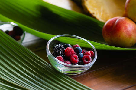 Close up bowl with berries on leaves