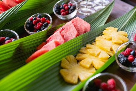 Fruit slices inside green leaves on buffet