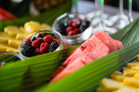 Hotel buffet table decoration with fruit slices - watermelon, pineapple and berries bowls at green leaves 스톡 콘텐츠