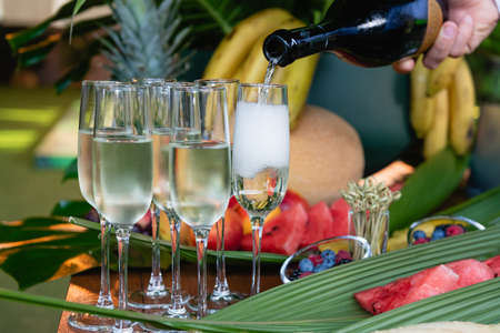 Male hand pour champagne drink in glasses