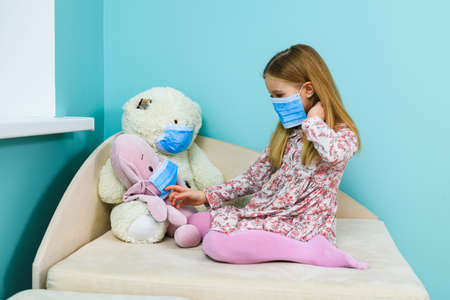 Little girl play with teddy bear and pig stuffed toys during home quarantine and remote study time, wearing three blue surgical face masks 스톡 콘텐츠
