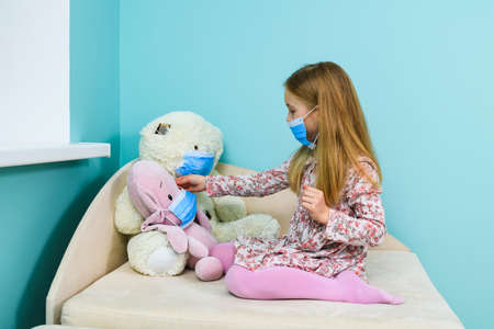 Little girl play with teddy bear and pig stuffed toys during home quarantine and remote study time, wearing three blue surgical face masks Imagens