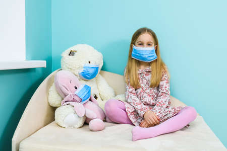 Primary school female child sit on couch with stuffed toys, all wearing blue face masks for virus protection at lockdown time Imagens