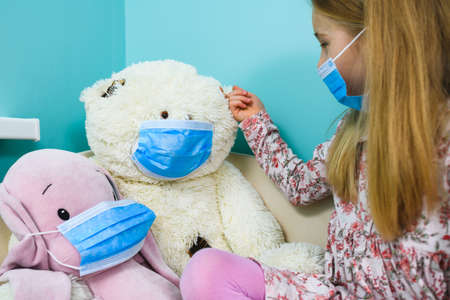Girl play and care about stuffed toys during quarantine, wearing protective blue disposable masks at blue indoor background Imagens