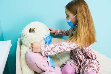 Small girl play at home during lockdown isolation, wearing blue surgical face mask on herself and stuffed toys