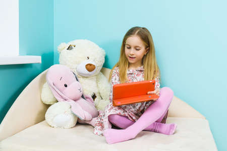 Small girl primary school age sit on sofa with teddy bear and looking at tablet screen inside light pastel home interior during lockdown isolation
