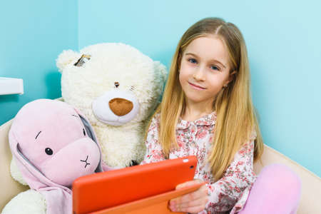 Elementary school age girl hold tablet in orange case and show screen to stuffed toys, home leisure during lockdown