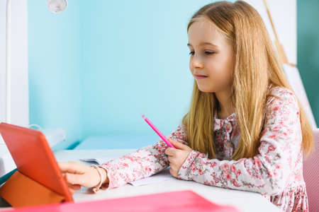 Elementary school age girl sit at desk and smiling for tablet screen with pen and paper notebook, remote study during home isolation