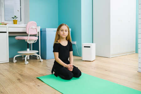 Small girl in black leotard sit on sport mat at home interior, workout training during self-isolation and quarantine