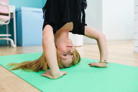 School girl stay on hands and head at sport mat during gymnastic training workout at home isolation quarantine time