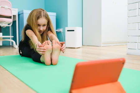Small girl stretch her legs on mat, looking at tablet screen, online remote sport gymnastics class from home during lockdown