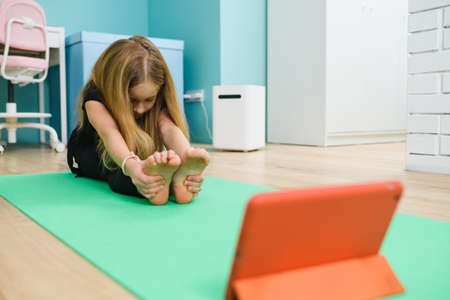 School girl sitting on sport mat, doing home workout stretching gymnastic exercises with tablet at quarantine lockdown