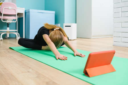 School blonde girl sit on sport mat at home interior during quarantine self-isolation and listen online gymnastic lesson from tablet