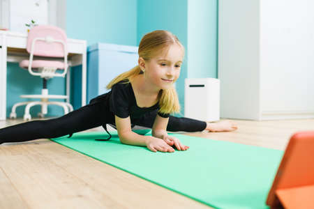 Primary school age sportive gymnast girl in black leotard stay in twine pose and look at tablet screen during online training at home 스톡 콘텐츠