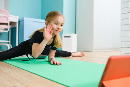 School girl gymnast in black leotard exercise at home mat, stay in twine pose during online lesson and wave hand to screen at isolation quarantine time