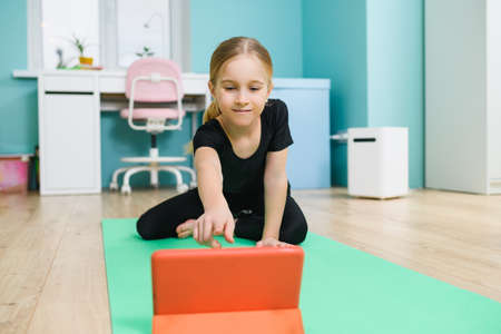 Positive school girl exercise workout at home online with tablet, sitting on sport mat at home interior during quarantine