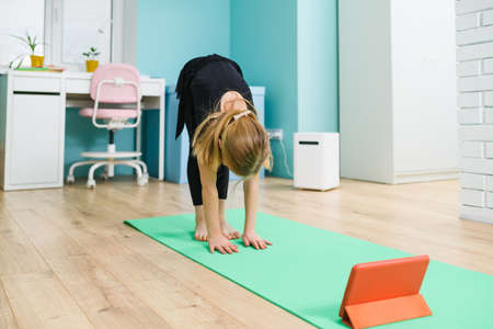 Small girl gymnast in black leotard stay on mat with head down, exercise at home with online lesson using tablet during isolation 스톡 콘텐츠
