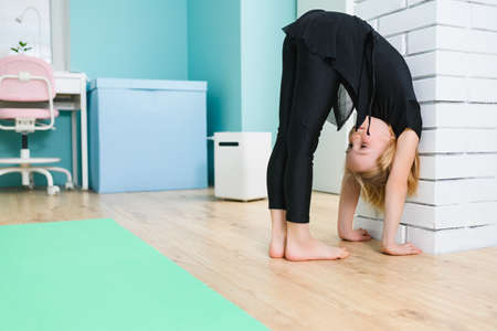 Small female gymnast in black leotard stand barefoot at home near bricks wall with hands and head down, workout training during quarantine