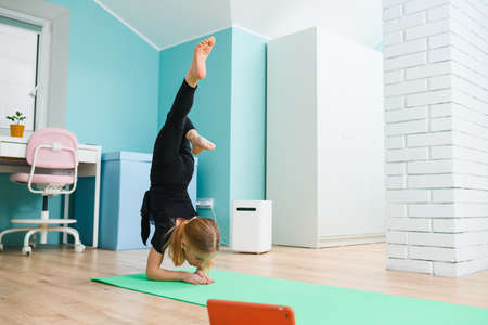 Small girl primary school age stay home on mat upside down on her elbows with tablet during online lesson