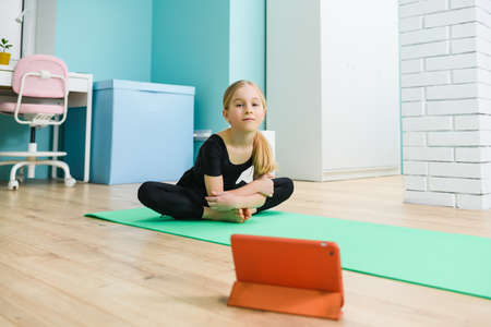Elementary school girl put sport mat and tablet on floor, wearing black leotard before start online remote gymnastic class during self-isolation at home