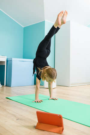 School girl in black leotard exercise gymnastics with online video class, stand on hands upside down on sport mat at home interior Imagens