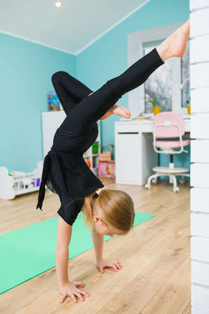 Female child in black leotard stand on hands with head down, lean on wall, activity training during self-isolation and social distancing 스톡 콘텐츠