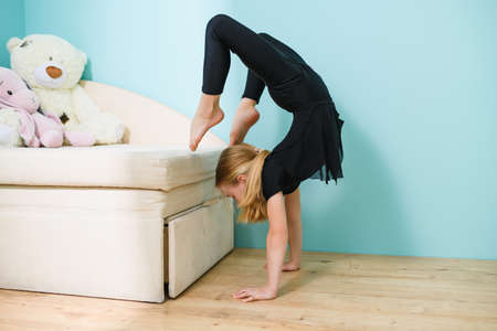 Sportive girl elementary school age in sportswear stand on hands upside down near couch during self-isolation