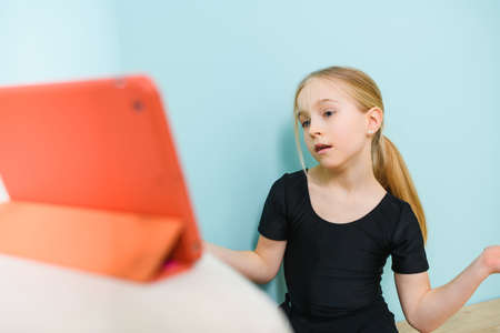 Little girl during video call, online class with tablet on desk looking at screen and communicate at social distancing, self-isolation time